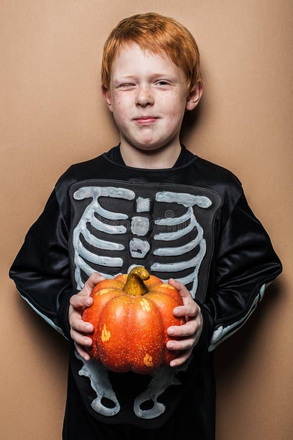 Giovane ragazzo rosso dei capelli che tiene una piccola zucca per Halloween fotografie stock libere da diritti