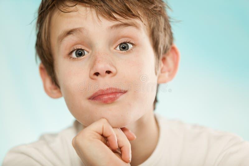 Giovane ragazzo scettico che alza le sue sopracciglia fotografia stock