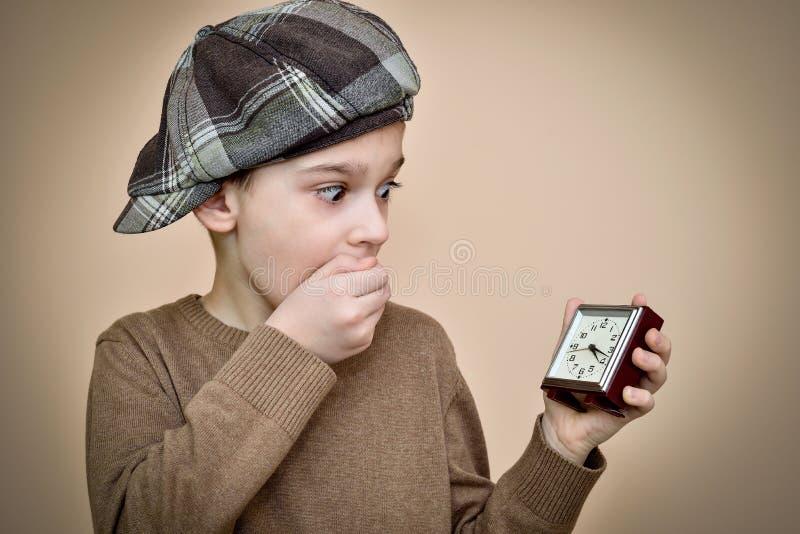 Giovane ragazzo sorpreso che esamina una sveglia fotografia stock
