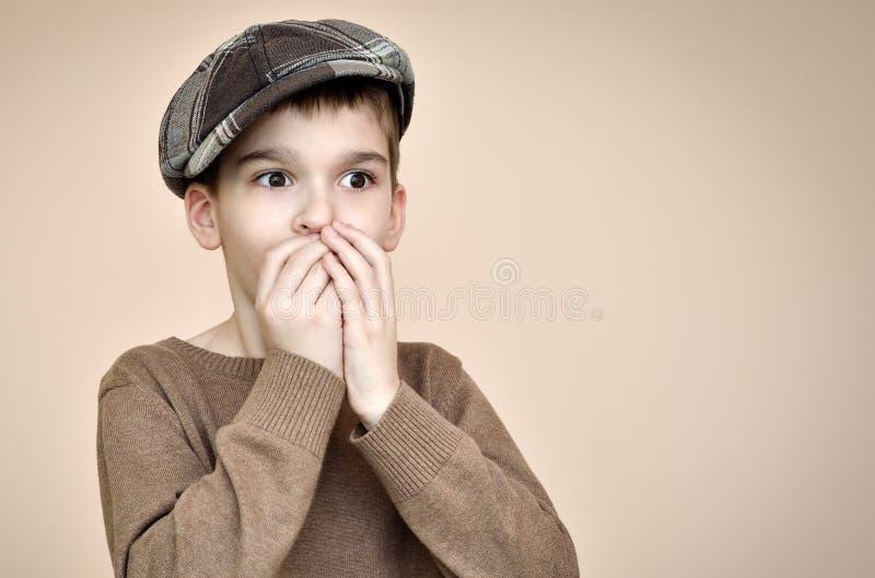 Giovane ragazzo sorpreso con il cappuccio che copre il suo bocca di mani immagine stock libera da diritti