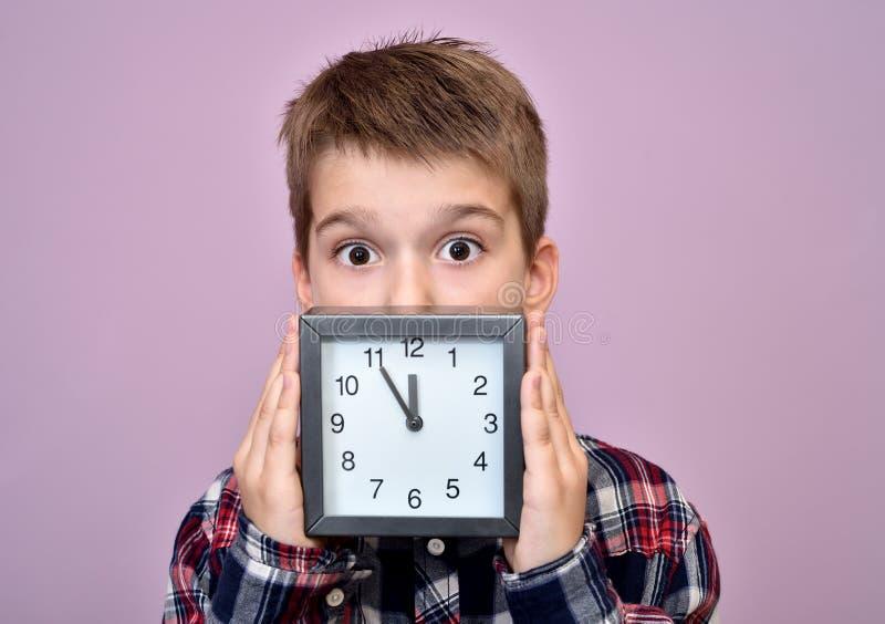 Giovane ragazzo sorpreso con un orologio fotografie stock