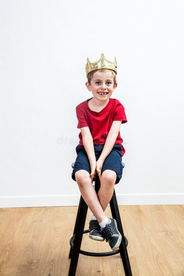 Giovane ragazzo sorridente rilassato con una corona messa sulle feci fotografie stock
