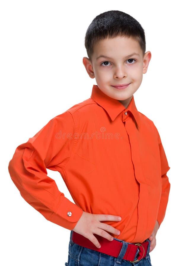 Giovane ragazzo sorridente in una camicia rossa immagine stock