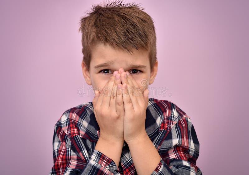 Giovane ragazzo spaventato con le mani sul suo fronte fotografie stock libere da diritti