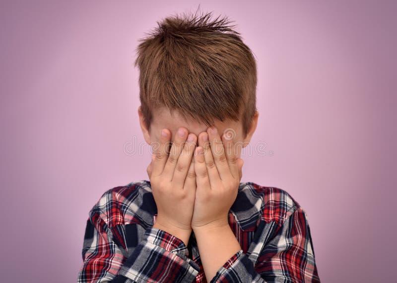 Giovane ragazzo spaventato con le mani sul suo fronte immagini stock