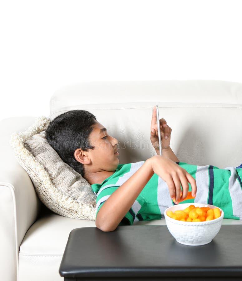 Giovane ragazzo su uno strato che fissa nella nel suoi compressa e cibo fotografia stock