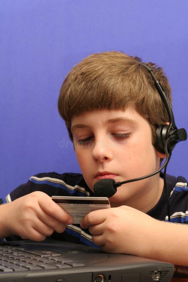 Giovane ragazzo sul calcolatore usando l'azzurro della carta di credito fotografia stock