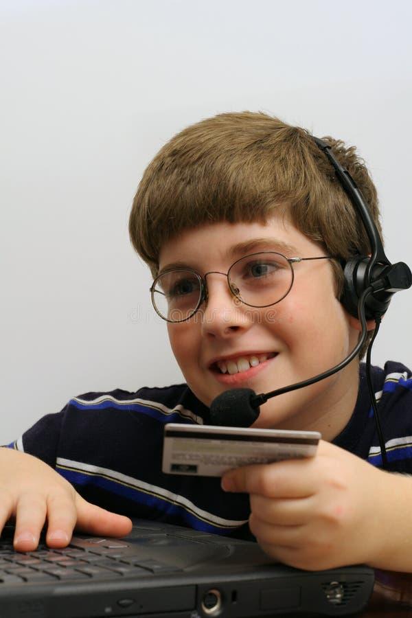 Giovane ragazzo sul calcolatore usando la carta di credito fotografie stock libere da diritti