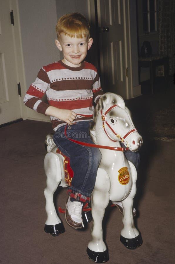 Giovane ragazzo sul cavallo di oscillazione fotografia stock libera da diritti