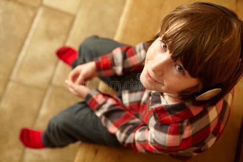 Giovane ragazzo sulla sede di legno che ascolta la musica immagini stock libere da diritti
