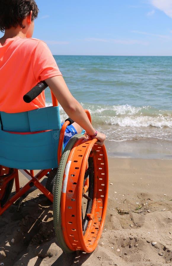 Giovane ragazzo sulla sedia a rotelle speciale con le ruote da muoversi sulla s immagine stock libera da diritti