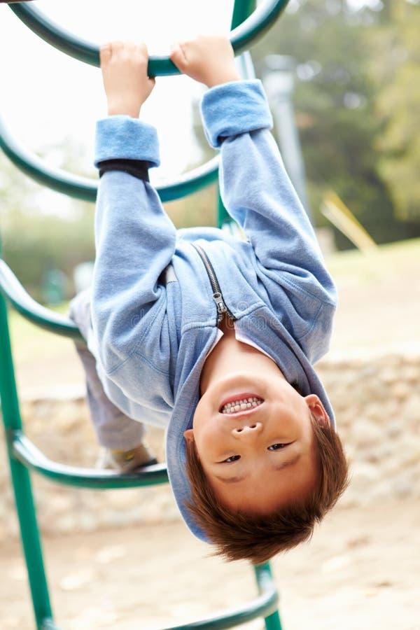 Giovane ragazzo sulla struttura di scalata in campo da giuoco fotografie stock