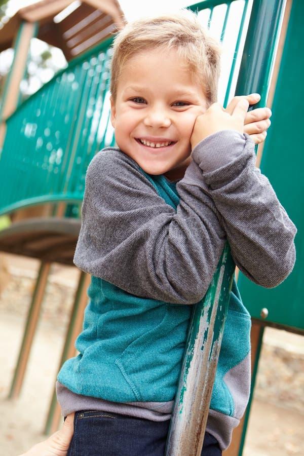 Giovane ragazzo sulla struttura di scalata in campo da giuoco immagini stock libere da diritti