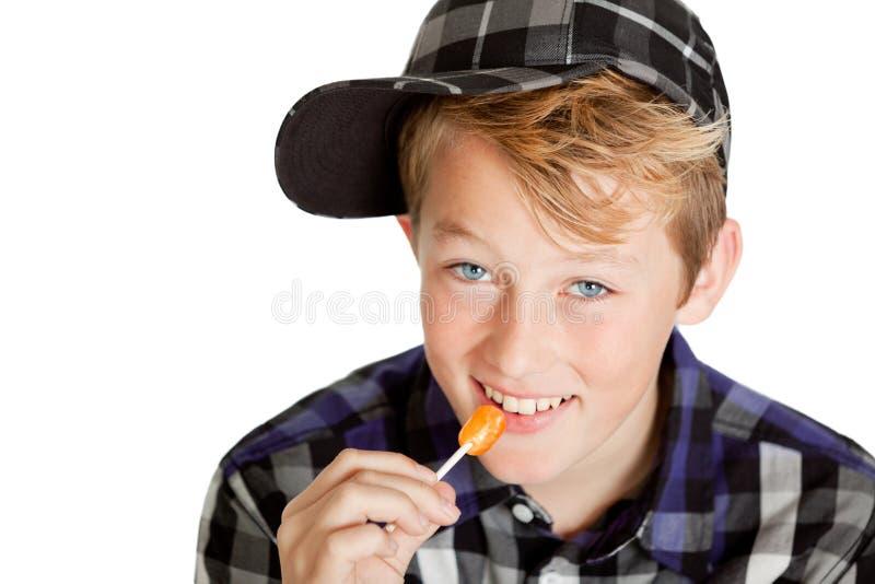 Giovane ragazzo sveglio che mangia una lecca-lecca fotografie stock libere da diritti