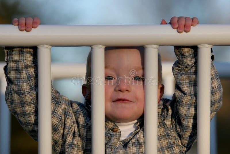 Giovane ragazzo sveglio che scruta tramite il cancello fotografie stock libere da diritti