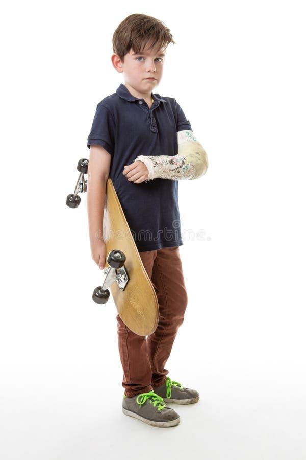 Giovane ragazzo sveglio che tiene un pattino immagini stock libere da diritti
