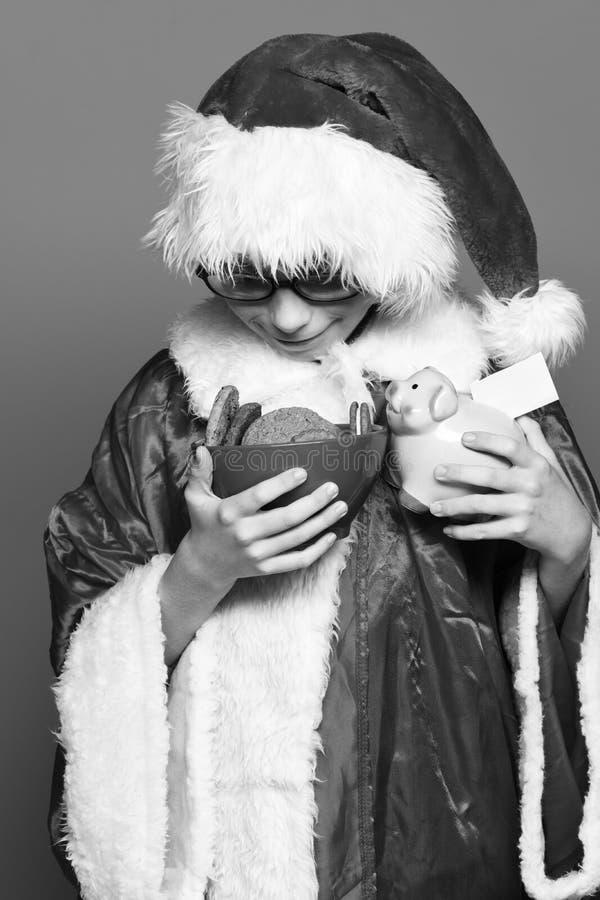 Giovane ragazzo sveglio del Babbo Natale con i vetri in cappello rosso di natale del nuovo anno e del maglione che tiene la banca immagini stock libere da diritti