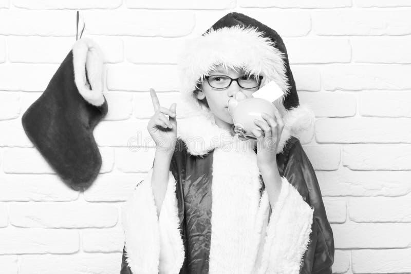 Giovane ragazzo sveglio del Babbo Natale con i vetri in cappello rosso del nuovo anno e del maglione con la calza decorativa di n fotografie stock