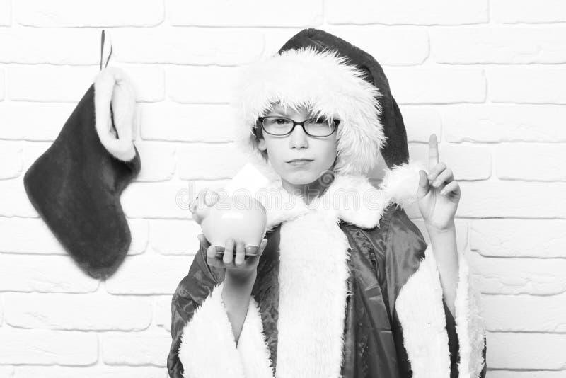 Giovane ragazzo sveglio del Babbo Natale con i vetri in cappello rosso del nuovo anno e del maglione con la calza decorativa di n immagine stock libera da diritti