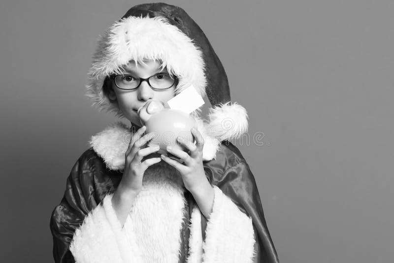 Giovane ragazzo sveglio del Babbo Natale con i vetri in maglione di natale e cappello di natale del nuovo anno che tengono e che  fotografie stock