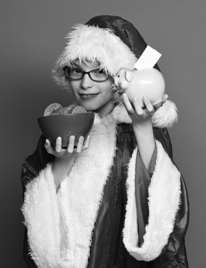 Giovane ragazzo sveglio del Babbo Natale con i vetri in maglione di natale e cappello di natale del nuovo anno che tengono la ban fotografia stock
