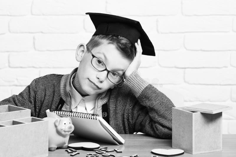 Giovane ragazzo sveglio dell'allievo in maglione grigio e vetri che si siedono allo scrittorio con la banca rosa del maiale di po fotografia stock libera da diritti