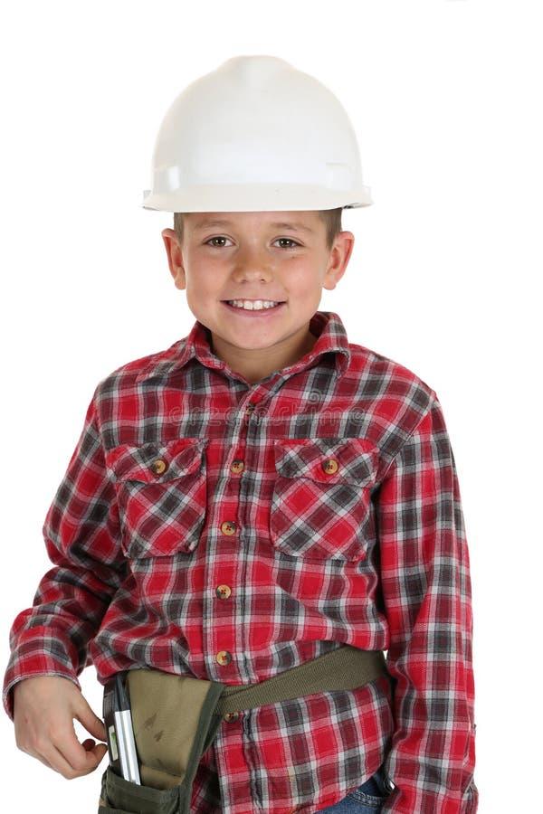 Giovane ragazzo in un sorridere dell'elmetto protettivo della costruzione immagine stock libera da diritti