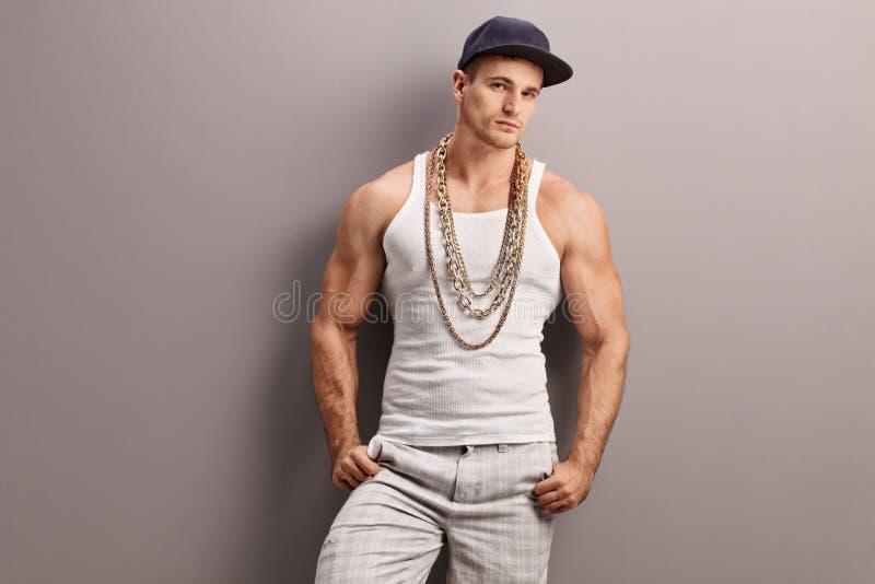 Giovane rapper muscolare che si appoggia una parete immagine stock