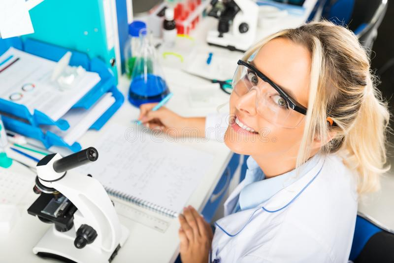 Giovane rapporto attraente di ricerca di scrittura dello scienziato della donna in fotografie stock