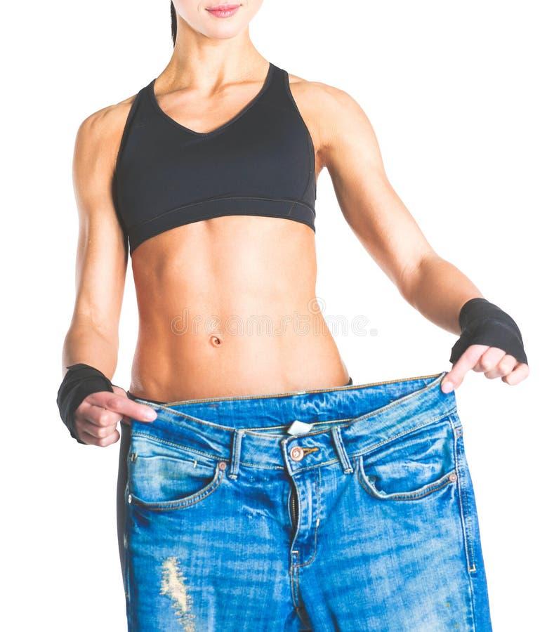 Giovane rappresentazione della donna di forma fisica che i suoi vecchi jeans immagine stock