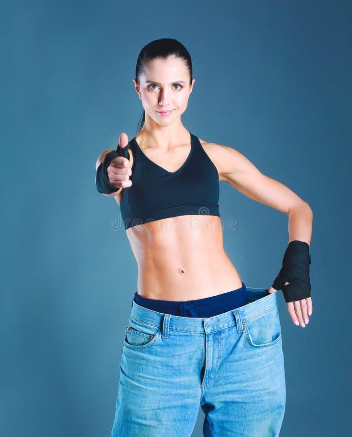 Giovane rappresentazione della donna di forma fisica che i suoi vecchi jeans e mostrare okay fotografie stock libere da diritti