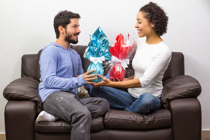 Giovane regalo delle coppie con le uova di Pasqua del cioccolato fotografia stock libera da diritti