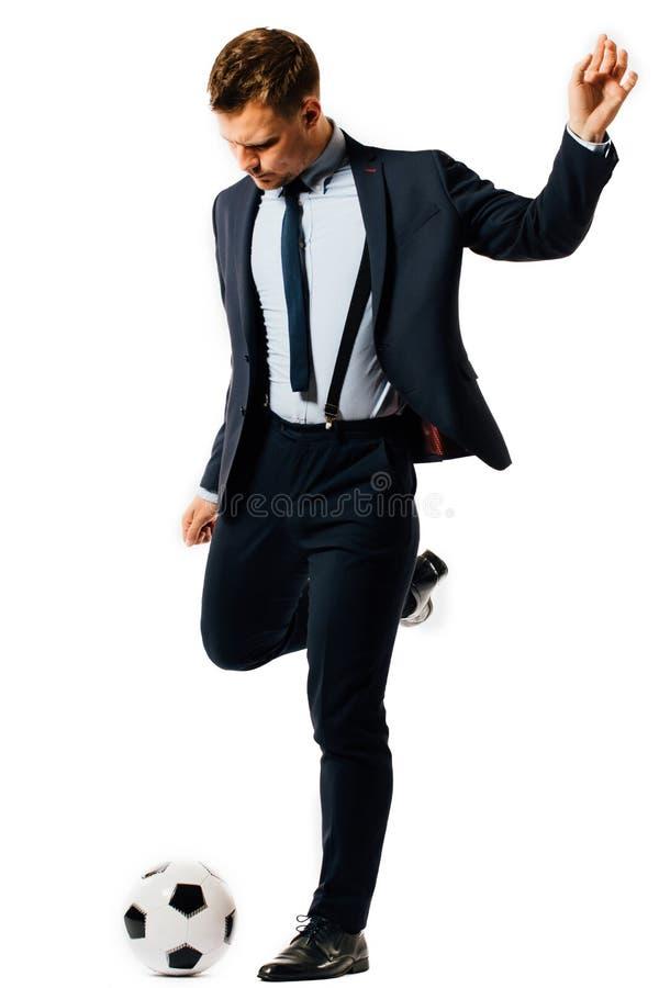 Giovane responsabile bello dell'uomo d'affari che dà dei calci ad un pallone da calcio su fondo bianco isolato fotografia stock libera da diritti
