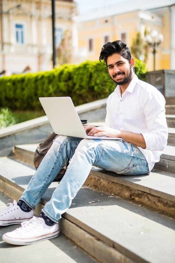 Giovane responsabile indiano bello che lavora al computer portatile mentre sedendosi all'aperto sulle scale nella via fotografia stock libera da diritti