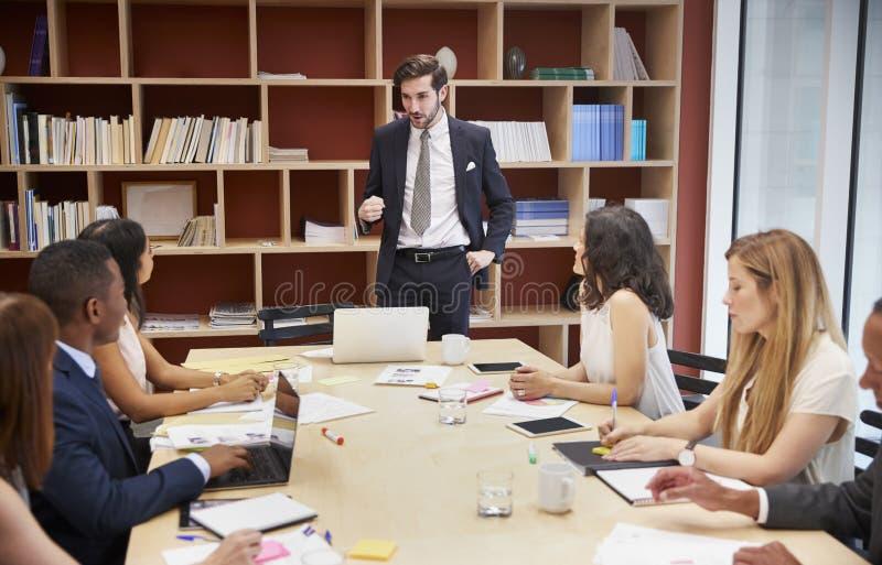 Giovane responsabile maschio che sta ad una riunione della sala del consiglio di affari immagini stock libere da diritti