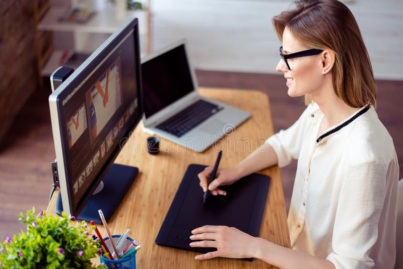 Giovane retoucher professionale che si siede alla tavola a casa ed al wo fotografia stock libera da diritti