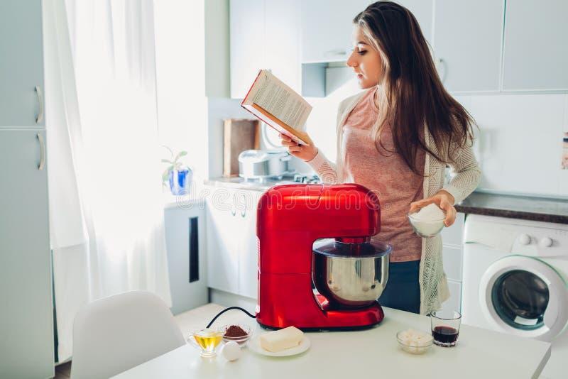 Giovane ricetta della lettura della casalinga per la cottura della torta in libro culinario Donna che per mezzo dell'unità di ela immagini stock