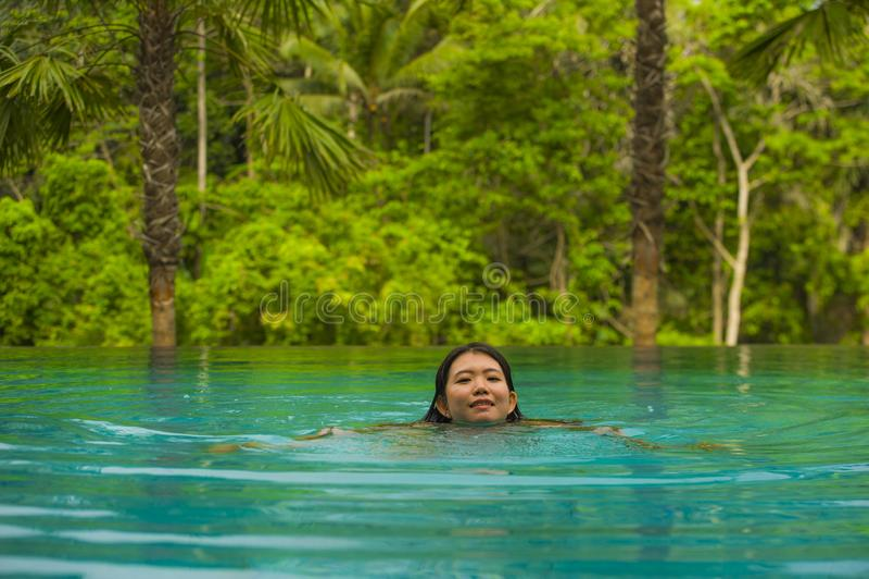 Giovane rilassamento coreano asiatico attraente e bello della donna felice a nuoto tropicale della stazione balneare allo stagno  immagine stock