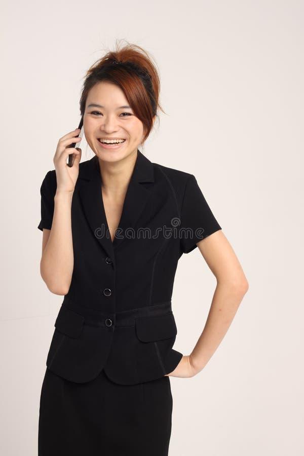 Giovane risata asiatica di signora soddisfatta di un telefono moble fotografie stock libere da diritti
