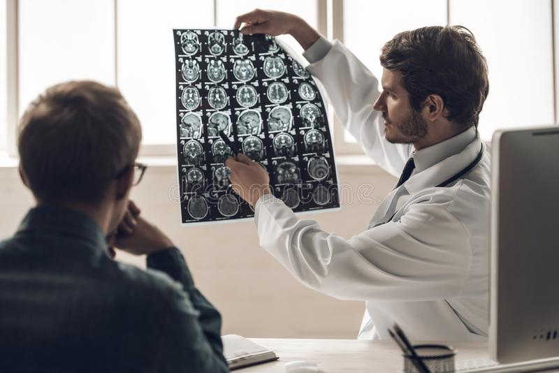 Giovane risonanza magnetica del dottore Showing del cervello al paziente fotografia stock libera da diritti