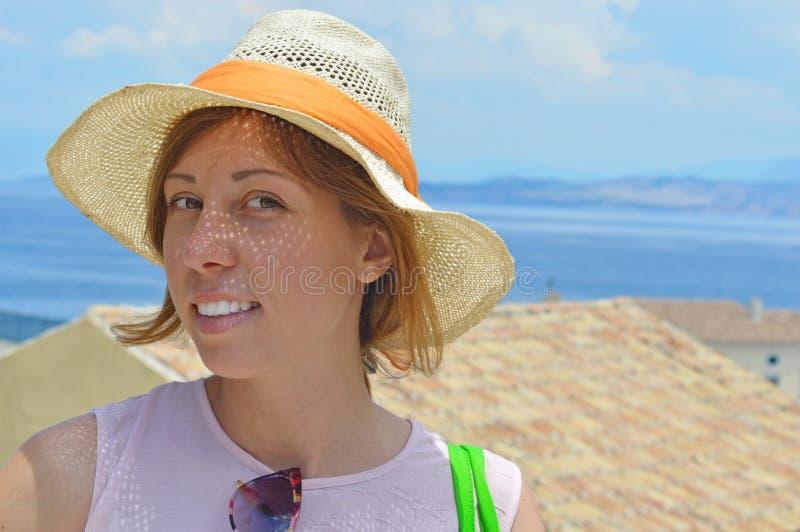 Giovane ritratto abbronzato felice della ragazza con il mare nel fondo fotografie stock
