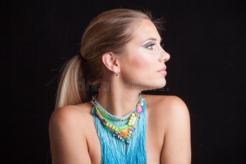 Giovane ritratto biondo della donna di bellezza con la grande collana blu con fotografia stock