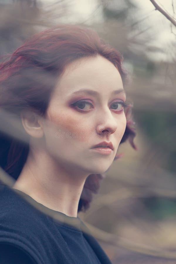 Giovane ritratto della donna degli occhi azzurri attraverso i colpi leggeri naturali all'aperto del vento del primo piano del ram fotografia stock