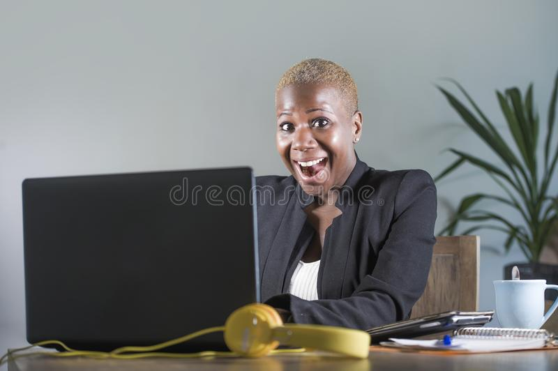 Giovane riuscita donna afroamericana nera attraente e felice nel lavoro del rivestimento di affari allegro allo scrittorio del co immagine stock libera da diritti