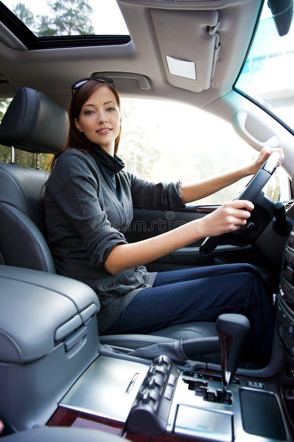 Giovane riuscita donna nella nuova automobile fotografia stock