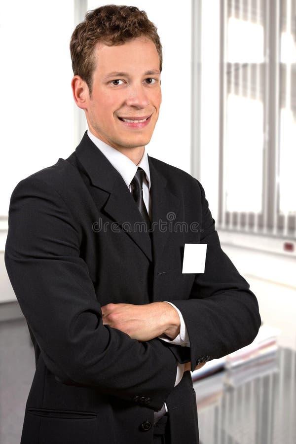 Giovane riuscito uomo d'affari che sorride nel suo ufficio fotografie stock