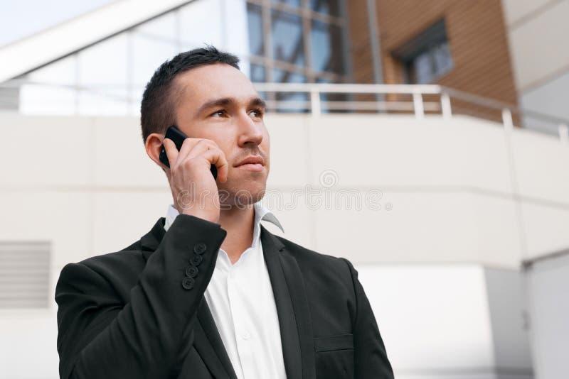 Giovane riuscito uomo in vestito nero che parla sul distogliere lo sguardo del telefono cellulare fotografie stock