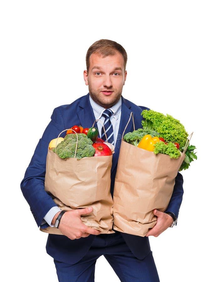 Giovane sacchetto della spesa della tenuta dell'uomo d'affari in pieno delle verdure isolate su fondo bianco fotografia stock libera da diritti
