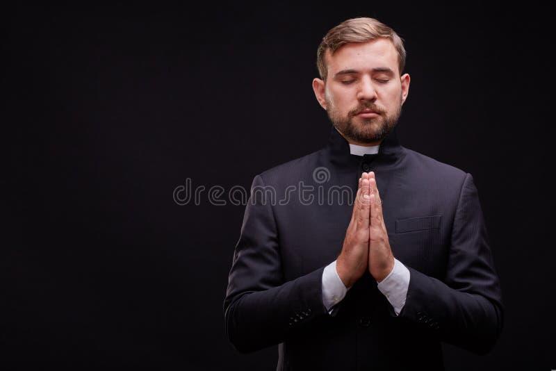 Giovane sacerdote bello con pane che posa su un fondo nero fotografie stock