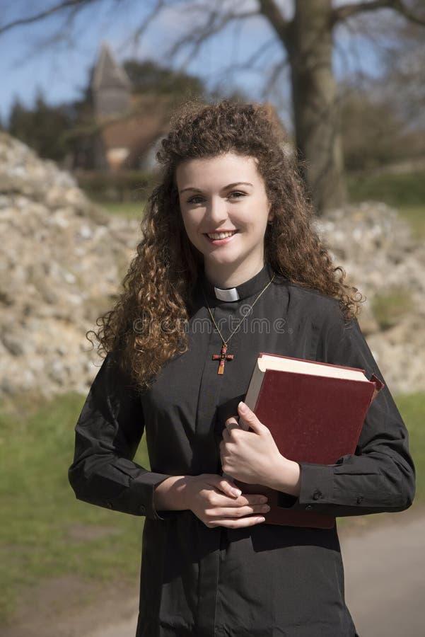 Giovane sacerdote che visita la sua parrocchia nella campagna fotografia stock